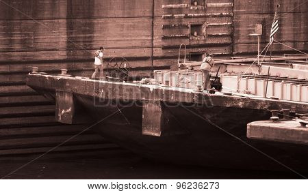 Barge Workers on a Large Barge. American Flag. Red Sepia.