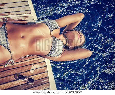 Beautiful woman in summer vacation, gorgeous model with perfect body lying down on the board of sailboat and tanning, enjoying luxury summer vacation