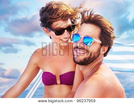 Portrait of happy cheerful cute couple having fun on sailboat, enjoying each other in romantic summer trip, spending honeymoon in the sea
