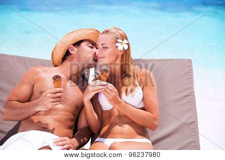 Loving couple on the beach, happy young family relaxing on sunbeds and refreshing cold tasty ice cream, handsome guy kissing his cute wife, happy summer holidays