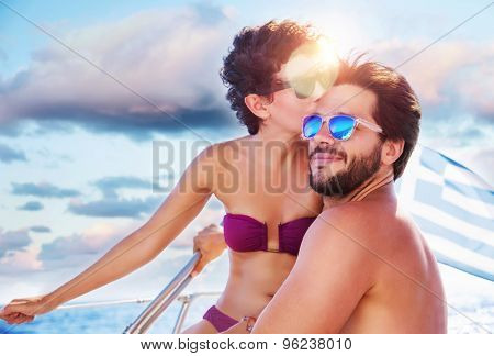 Portrait of happy cheerful cute couple kissing on sailboat, enjoying each other in romantic summer trip, spending honeymoon in the sea