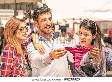 Group Of Happy Young People At The Weekly Cloth Market Looking At Female Underwear - Best Friends