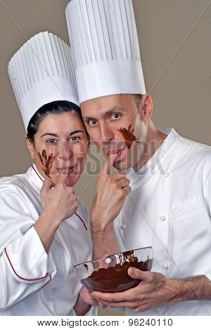 Funny young cook couple tasting chocolate cream.