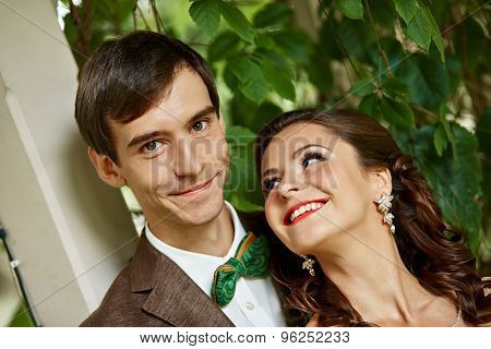 Closeup Portrait Of Young Couple In Green Park. Girl Looks At The Man With Eyes Full Of Love And Smi