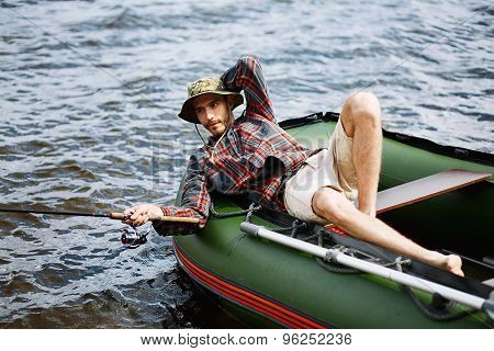 Young Happy Man On Vacation Lying In The Boat Smile And Fishing