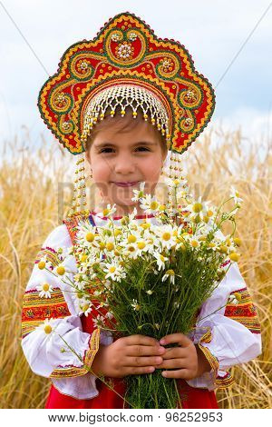 Girl In The Russian National Sundress And A Kokoshnik To Stand In The Field With A Bouquet Of Camomi