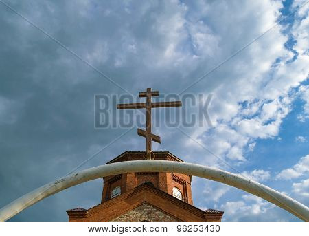 White Semi-circular Arch Of Iron Pipe With Dark Orthodox Cross Over It Before The Tower Of The Ancie