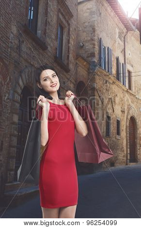Beautiful Brunette Woman In A Red Dress Is Holding Fancy Shopping Bags. Italy Cityscape.