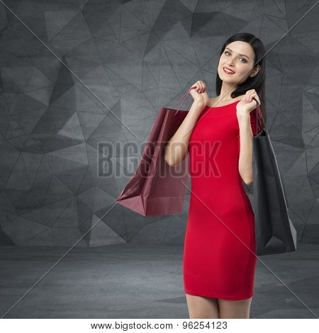 Beautiful Brunette Woman In A Red Dress Is Holding Fancy Shopping Bags. Contemporary Background.