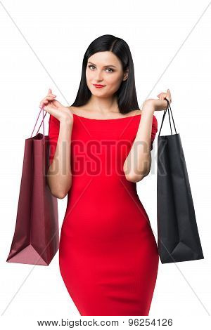 Beautiful Brunette Woman In A Red Dress Is Holding Fancy Shopping Bags. Isolated.