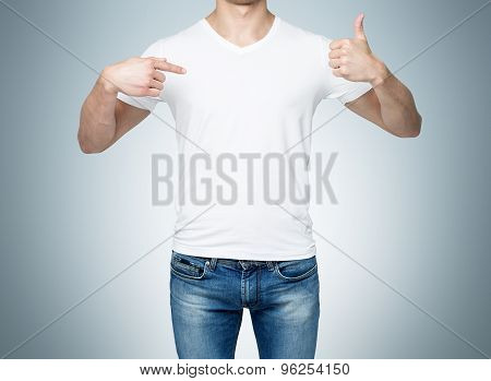 Close-up Of A Man Pointing His Finger To A Blank T-shirt, And The Thumb Up. Blue Background.