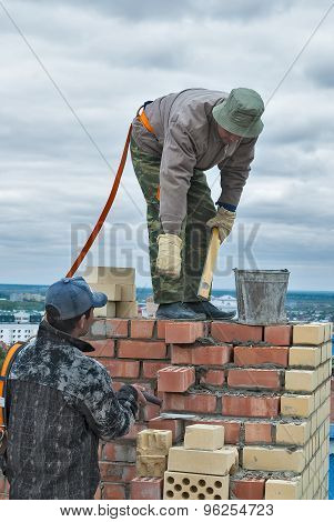 Bricklayers work on high house construction