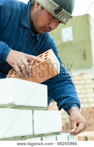 Bricklayer works on house construction