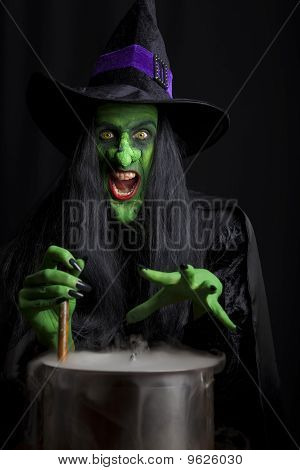 Scary witch stirring a smokey cauldron.