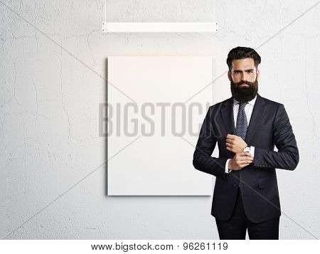 man wearing suit and blank poster on a wall
