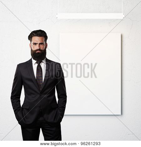 Bearded bussines man wearing suit and blank poster on a wall