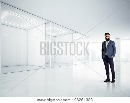 Blank office interior with big windows and young bussinesman