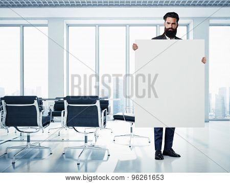 Bearded businessman with white canvas at contemporary office