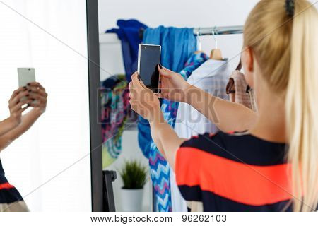 Blonde Woman Standing Near Wardrobe Rack Full Of Clothes And Mirror
