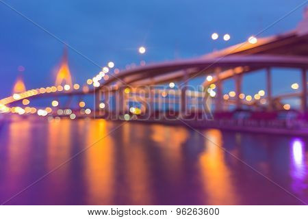 Bokeh lights of City highway and Suspension bridge with water reflection