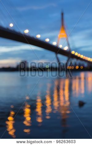 Blurred bokeh lights of Suspension bridge with water reflection