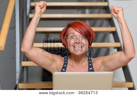 Happy Adult Woman With Laptop Raising Her Arms