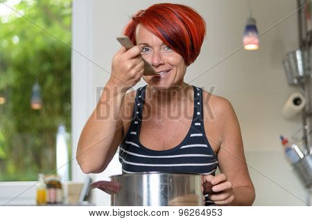 Adult Woman Tasting Her Recipe Using Wooden Ladle