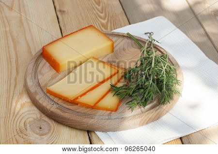 Sliced cheese on wooden board with dill and rosemary