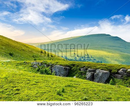 Mountain Peak Behind Hillside With Boulders At Sunrise