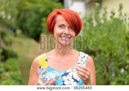 Happy Redhead Woman Holding A Plastic With Berries