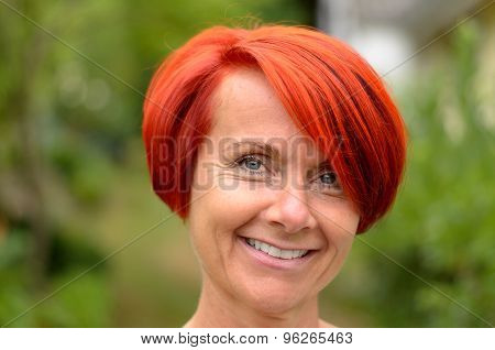 Smiling Adult Redhead Woman Against Hazy Greenery