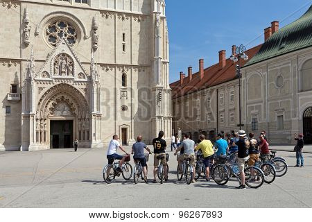 ZAGREB, CROATIA - MAY 13, 2015: Group of tourists on bicyles in front of the Zagreb Cathedral on Kaptol. Cathedral is dedicated to the Assumption of Mary and to kings Stephen and Ladislaus.