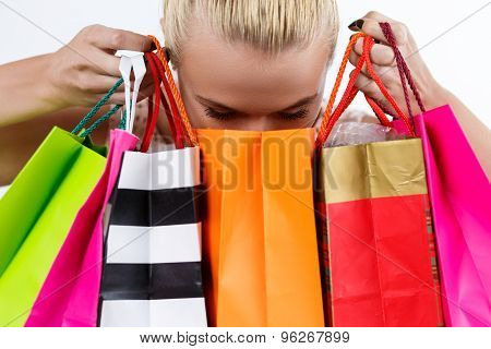 Blond Woman Inspecting Content Of Colored Paper Bags With Fresh Buyings