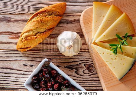 Mediterranean food bread loaf garlic olives and cheese slices on rustic wood