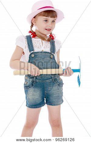 Caucasian little girl holding a hoe