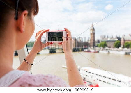 Young woman taking pictures of Big Ben, London UK with smartphone. Mobile photography, tourism in England, Great Britain concepts.