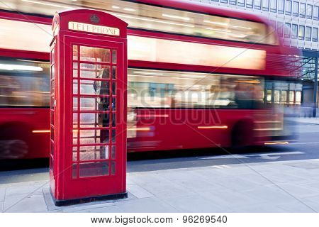 London, UK. Red telephone booth and red bus passing in motion blur. Symbols of Great Britain, United Kingdom, England.