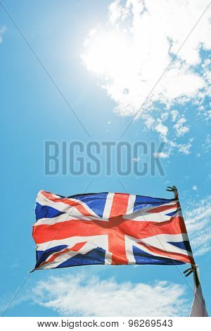 The Union Jack, the national flag of the United Kingdom waving on wind against blue sunny sky