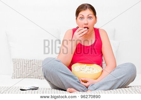Female Attentively Watching Tv And Eating Popcorn