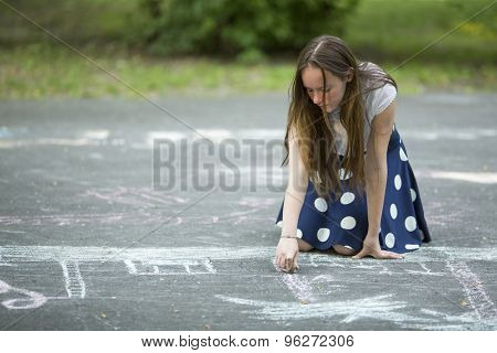Lovely teen girl draws with chalk on the pavement.