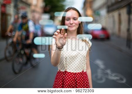 Young cute teen girl in the street presses an imaginary button in the air. Buttons with place for your text.