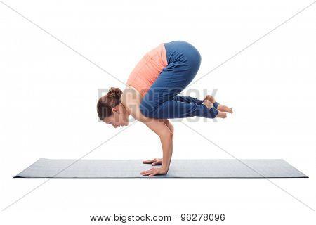 Beautiful sporty fit yogini woman practices yoga asana Bakasana - crane pose arm balance isolated on white