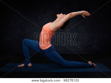 Beautiful sporty fit yogini woman practices yoga asana  Anjaneyasana - low crescent lunge pose in surya namaskar on dark background