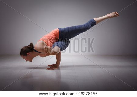 Beautiful sporty fit yogini woman practices yoga asana eka pada koundinyasana 1 - pose 1 dedicated to sage Koundinya pose in studio
