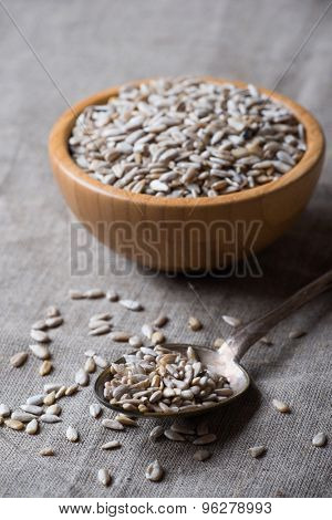 Raw peeled sunflower seeds in spoon over linen napkin