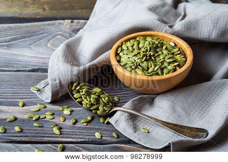 Raw Organic Pumpkin Seeds in vintage metal spoon over wooden background
