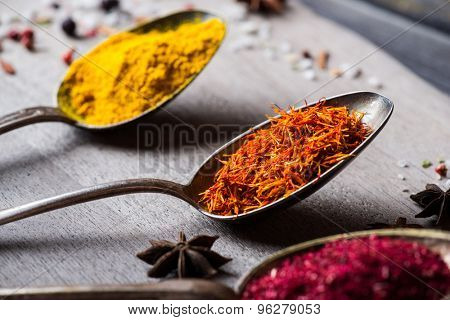 Different spices selection in old metal spoons over wooden background