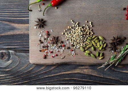 Spices over wooden background with empty place for text. Cardamon, pepper corns, anise.