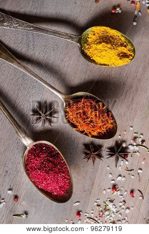 Different spices selection in old metal spoons over wooden background. Curry, Saffron, turmeric, sumac and other.
