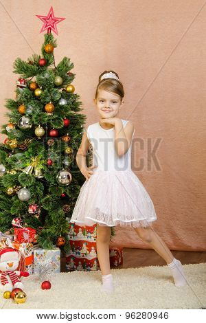 Five-year Girl Is Standing At The Christmas Tree